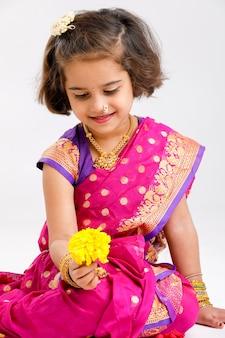 Śliczna mała indyjska / azjatykcia dziewczyna robi kwiatu projektowi