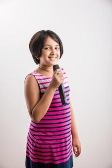 Śliczna mała indyjska dziewczyna śpiewająca do mikrofonu, stojąca na białym tle na białym tle