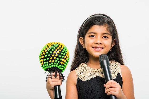Śliczna mała indyjska dziewczyna śpiewająca do mikrofonu, wyizolowana na białym tle