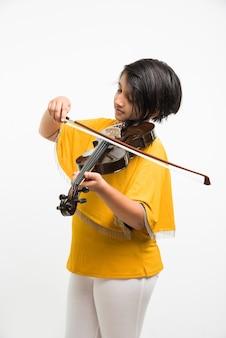 Śliczna mała indyjska lub azjatycka dziewczyna gra na skrzypcach, wyizolowana na białym tle
