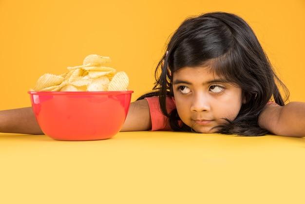 Śliczna mała indyjska lub azjatycka dziewczyna jedząca chipsy lub wafle ziemniaczane w dużej czerwonej misce, na żółtym tle