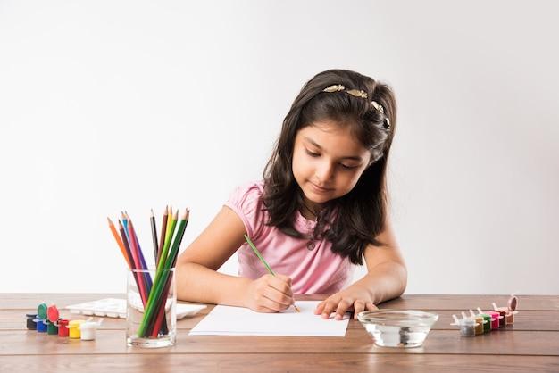 Śliczna mała indyjska lub azjatycka dziewczyna koloruje, rysuje lub maluje kolorami, ołówkami itp