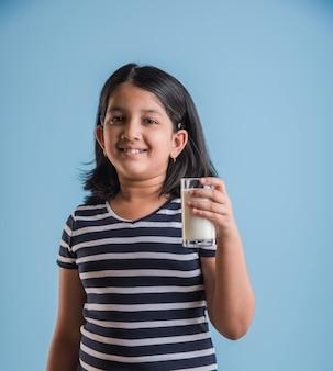 Śliczna mała indyjska lub azjatycka wesoła dziewczynka trzymająca lub pijąca szklankę pełną mleka, odizolowana na kolorowym tle