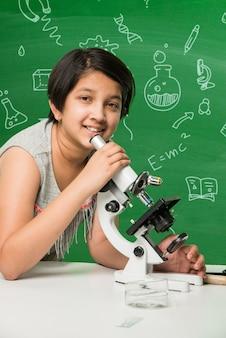 Śliczna mała indyjska uczennica azjatycka eksperymentuje lub studiuje naukę w laboratorium, na tle zielonej tablicy z gryzmołami edukacyjnymi