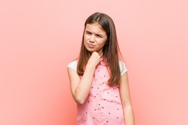 Śliczna mała kobieta cierpi na ból gardła z powodu wirusa lub infekcji.