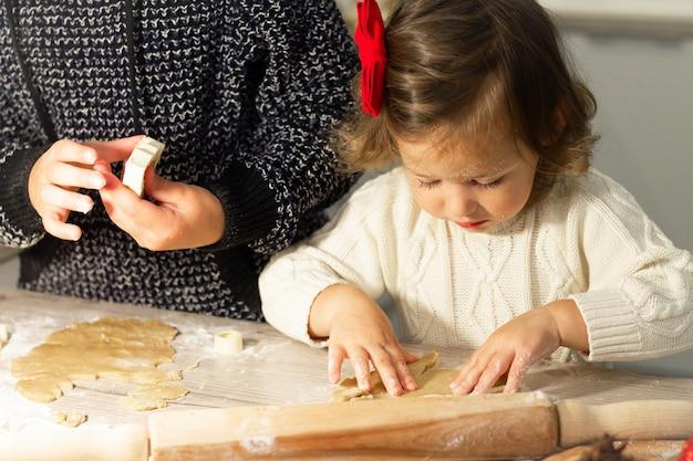 Śliczna mała poważna dziewczynka 2-4 z czerwoną kokardką przygotowuje świąteczne pierniki w noworocznej kuchni.