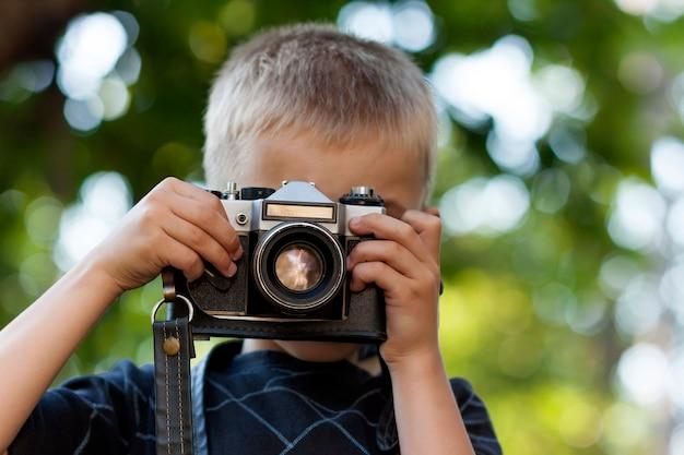 Śliczna mała szczęśliwa chłopiec z rocznik fotografii kamerą outdoors