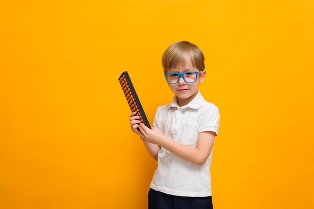 Śliczna mała szkolna chłopiec trzyma abakusa na kolorze żółtym w szkłach