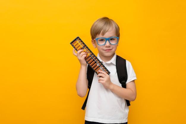 Śliczna mała szkolna chłopiec trzyma abakusa w szkłach. arytmetyka mentalna