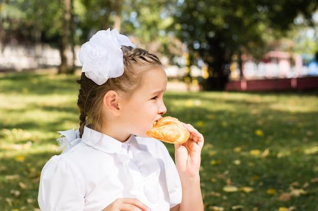 Śliczna mała uczennica gryzie kawałek rogalika na pikniku w parku. szkolne posiłki