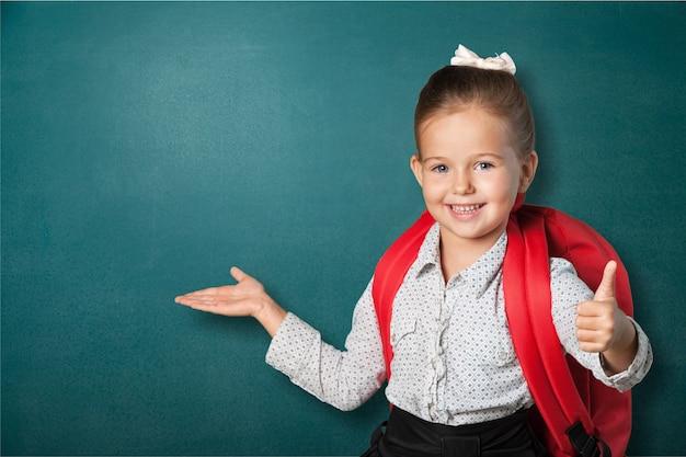 Śliczna mała uczennica na tle tablicy