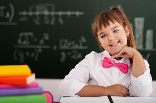 Śliczna mała uczennica siedzi w klasie z jej książkami