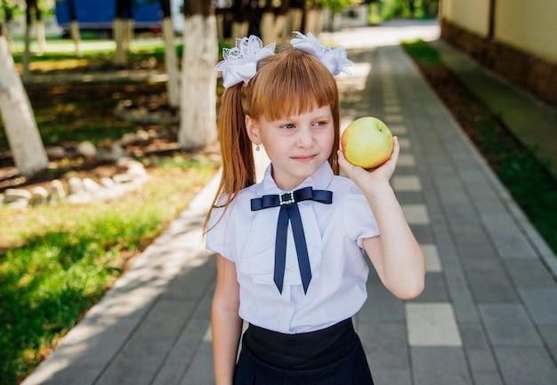 Śliczna mała uczennica stoi w parku lub na szkolnym dziedzińcu i trzyma w rękach zielone jabłko.