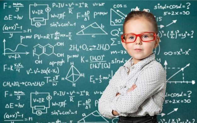 Śliczna mała uczennica w okularach na tle tablicy