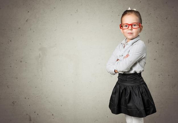Śliczna mała uczennica w okularach, wskazując na tle