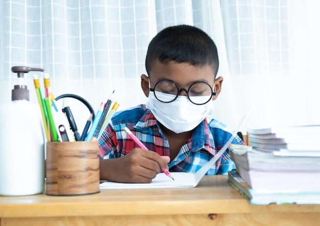 Śliczna mała uczniowska chłopiec studiuje w domu