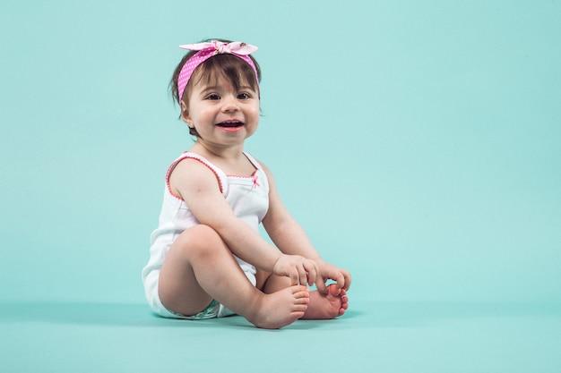 Śliczna mała uśmiechnięta dziewczyna z menchiami ono kłania się w włosianym obsiadaniu w studiu pozuje błękit