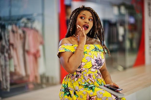 Śliczna mała wysokość amerykanina afrykańskiego pochodzenia dziewczyna z dredami, jest ubranym przy kolorową żółtą suknią, siedzi na ławce w centrum handlowym z zdziwioną twarzą.