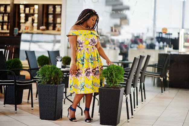 Śliczna mała wysokość amerykanina afrykańskiego pochodzenia dziewczyna z dredami, jest ubranym przy kolorową żółtą suknią, stoi na kawiarni w centrum handlowym.