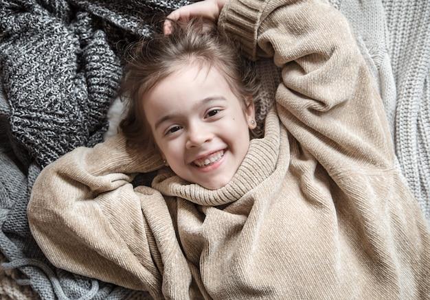 Śliczna mała zabawna dziewczyna w sweter z dzianiny.