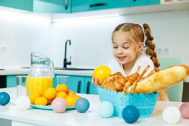 Śliczna mała zabawna, zabawna dziewczyna szczęśliwie trzymająca pomarańczowe pomarańcze, z kuchnią w tle
