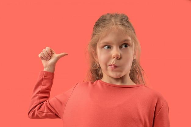 Śliczna mała zaskoczona dziewczyna w koralowej sukience z długimi włosami, uśmiechając się