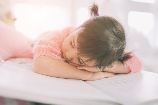 Śliczna małe dziecko dziewczyna czyta książkę w domu. śmieszne piękne dziecko zabawy w pokoju dziecięcym.