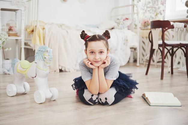 Śliczna małe dziecko dziewczyna czyta książkę w sypialni. dziecko z koroną, siedząc na łóżku w pobliżu okna