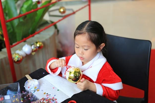 Śliczna małe dziecko dziewczyna robi bożenarodzeniowemu balowemu dekoracja ornamentowi