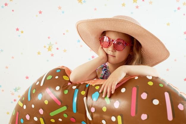 Śliczna małe dziecko dziewczyna w kapeluszu z nadmuchiwanym pierścionkiem na kolor ścianie. poddaj kwarantannie letnie wakacje w domu