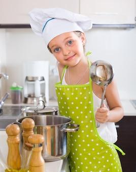 Śliczna małej dziewczynki kuchnia w domu