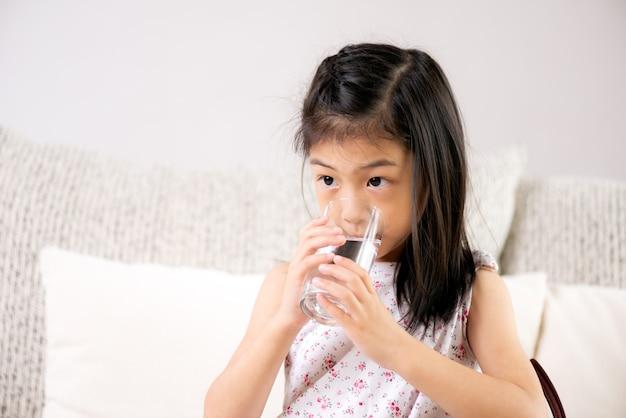 Śliczna małej dziewczynki woda pitna na kanapie w domu. pojęcie opieki zdrowotnej