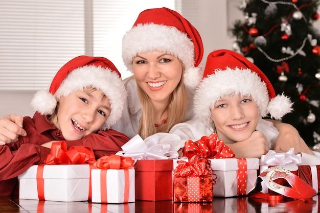 Śliczna mama i jej dzieci w czapkach mikołaja z prezentami