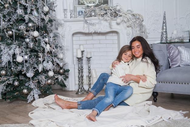 Śliczna mama i śliczna córeczka w białych przytulnych swetrach bawią się i przytulają pod udekorowaną choinką. świąteczne klasyczne wnętrze domu z kominkiem i szarą sofą.