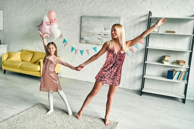 Śliczna mama i urocza urocza córeczka noszą podobną odświętną sukienkę, tańczą i bawią się z wielkimi emocjami, przyjęcie urodzinowe.