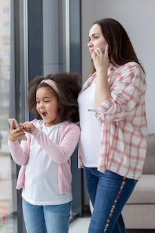Śliczna matka rozmawia przez telefon obok jej córki