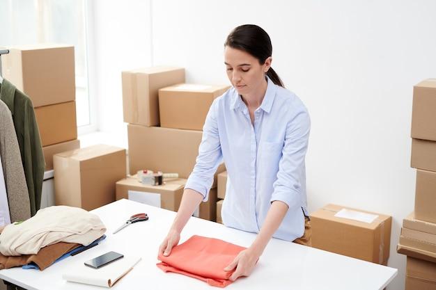 Śliczna menadżerka sklepu internetowego przygotowująca jedno z zamówień klientów i składana pulower przed zapakowaniem