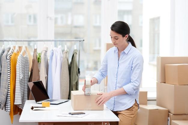 Śliczna menadżerka sklepu internetowego z zaklejanym pudełkiem z zamówieniem klienta taśmą klejącą przed wysłaniem