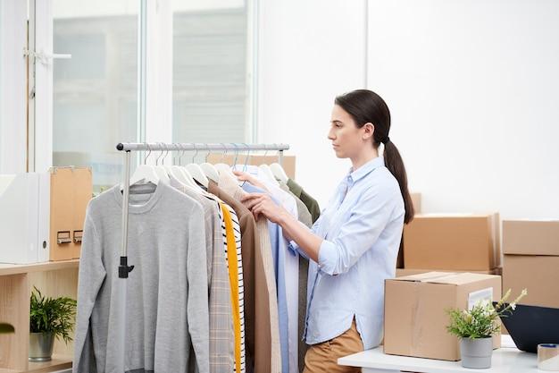Śliczna menadżerka współczesnego internetowego sklepu z odzieżą codzienną, która wybiera ubrania dla klientów stojąc przy szafie w biurze