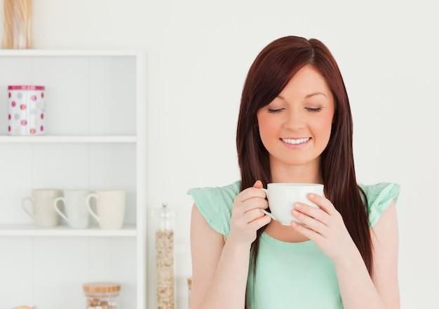 Śliczna miedzianowłosa kobieta ma jej śniadanie w kuchni