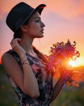 Śliczna młoda atrakcyjna dziewczyna z bukietem kolorowych kwiatów w dłoniach i czarnym kapeluszu. wieczorny spacer na łonie natury podczas zachodu słońca. zamyślony wygląd. romantyczna atmosfera.