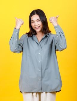 Śliczna młoda azjatycka kobieta na koszuli z długim rękawem pewnie stojąca za żywym portretem wycinanki modowej dziewczyny, uśmiechnięta i szczęśliwie kciuki do góry, aby zagwarantować doskonałą promocję sukienki
