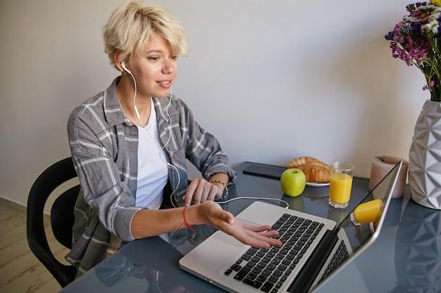 Śliczna młoda blond kobieta w zwykłym ubraniu siedzi przy stole obok otwartego laptopa, gestykuluje i rozmawia z kimś przez skype ze słuchawkami