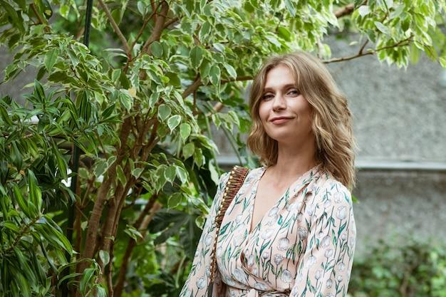 Śliczna młoda blondynka pozuje i uśmiecha się wśród zieleni w szklarni