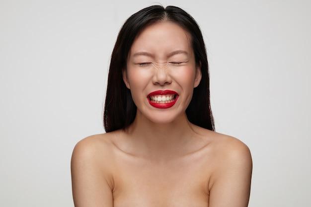 Śliczna młoda brunetka kobieta z przypadkową fryzurą, trzymając oczy zamknięte i marszczącą brwi, uśmiechając się radośnie, odizolowane na białej ścianie