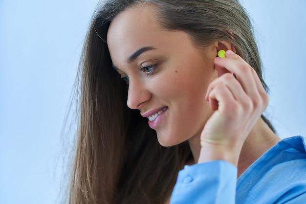 Śliczna młoda brunetki kobieta używa zatyczka do uszu. ochrona przed hałasem dla lepszego snu