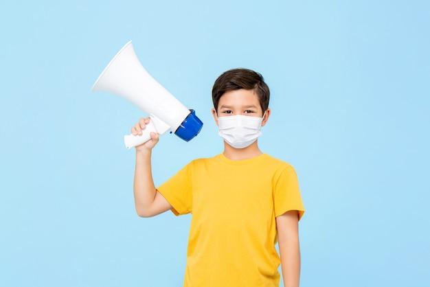 Śliczna młoda chłopiec jest ubranym medycznego maskowego mienie megafon odizolowywający