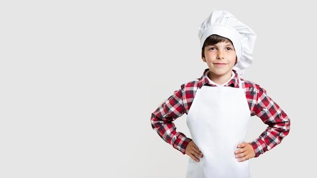 Śliczna młoda chłopiec pozuje jako szef kuchni