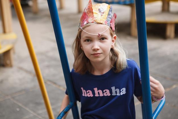 Śliczna młoda dziewczyna bawiąca się na huśtawce na playgorund w parku