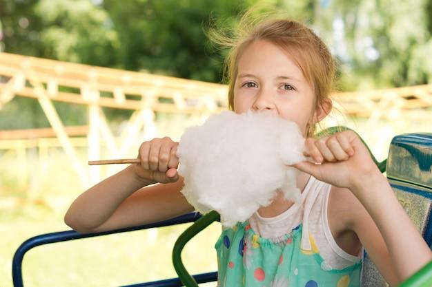 Śliczna młoda dziewczyna chowająca kulkę waty cukrowej
